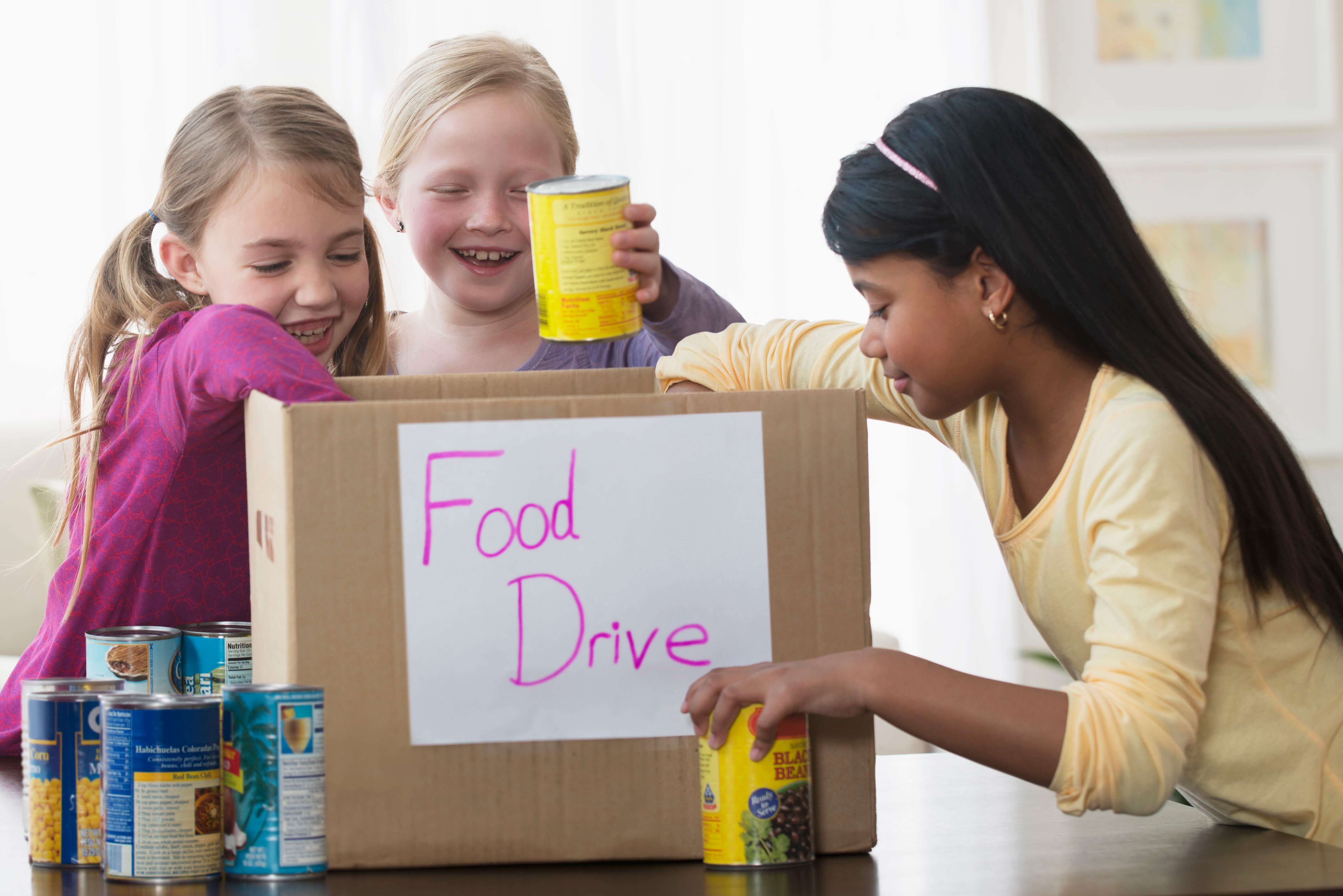 Girls placing cans of food in a donation box