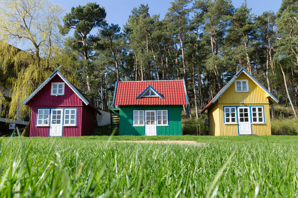 three multi-colored small houses on the lawn