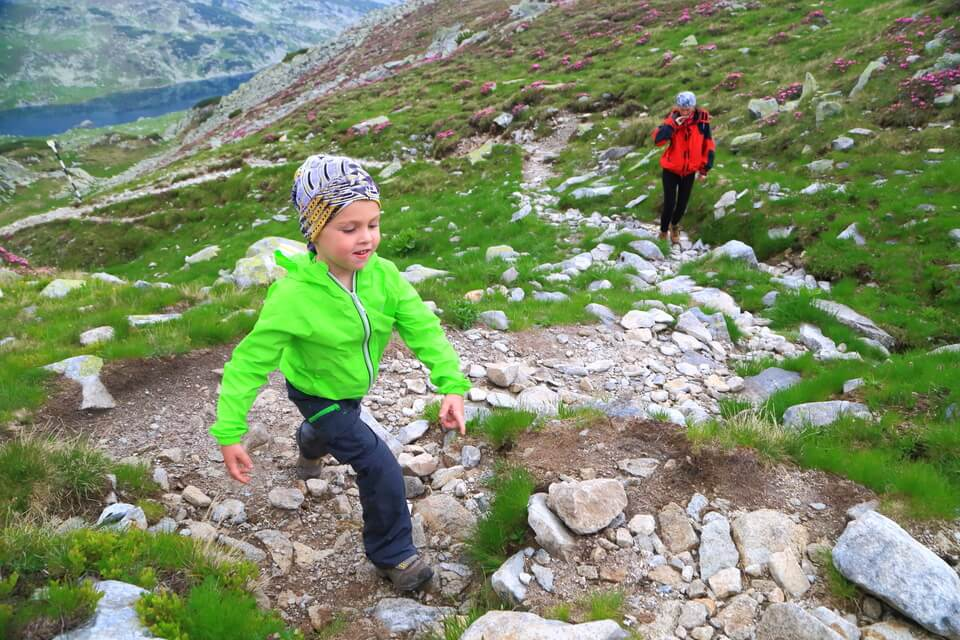boy and his mother hiking on a mountain trail