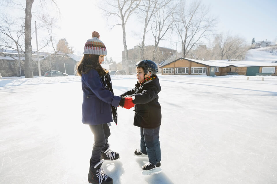 Siblings ice-skating on outdoor rink