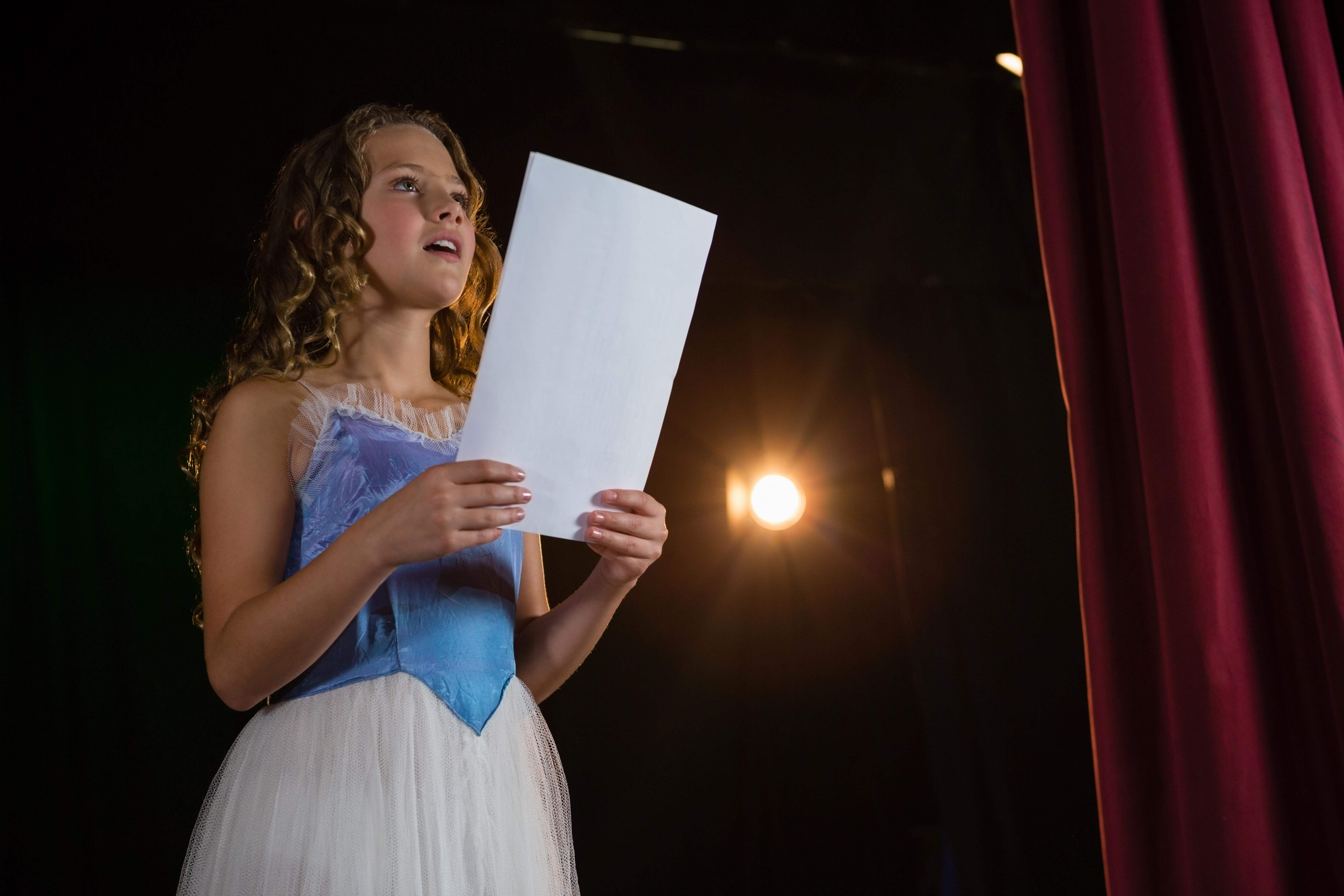 A girl reads from a script while acting in a play.
