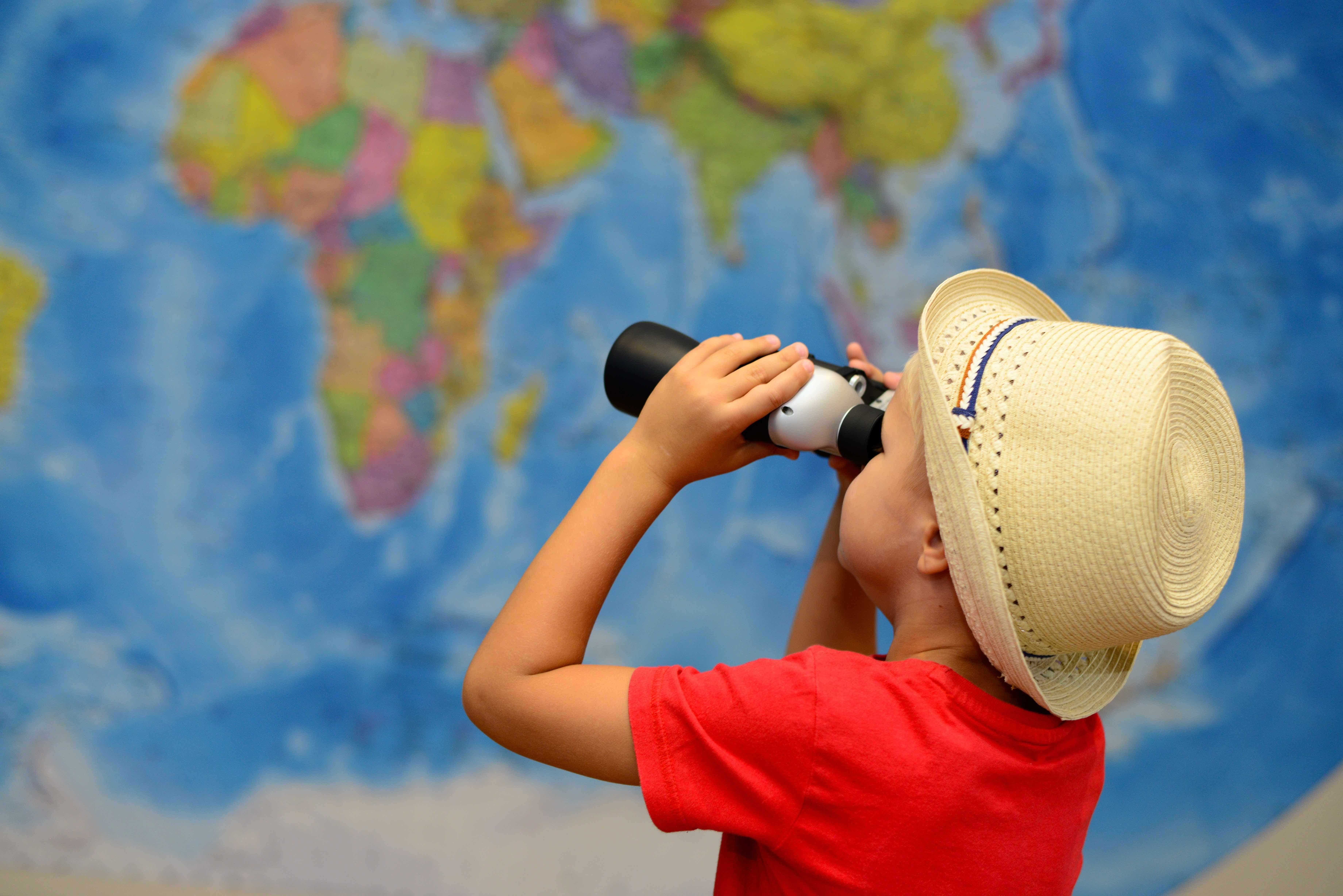 A boy looks at a map of the world through his binoculars.