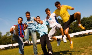Group of teenage boys, friends on a soccer field