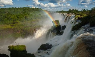 Rainbow appears between a waterfall at Iguazu National Park in Misiones, Argentina