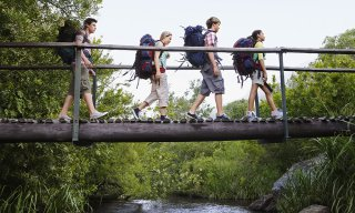 Four teenagers (16-17 years old) backpacking in forest crossing wooden bridge, side view