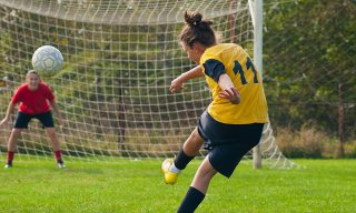 Girl kicking soccer ball toward goalie