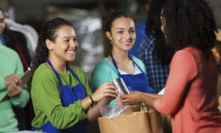 Teen girls volunteering at food bank, receiving donated groceries