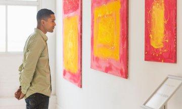 Man looking at paintings in modern art gallery
