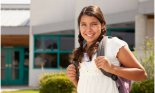 Hispanic girl wearing backpack in front of school