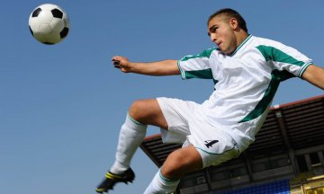 Low angle view of young male soccer player performing side volley kick in mid-air