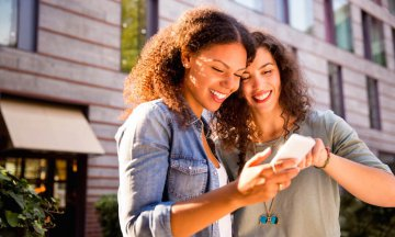 Girl friends look at smartphone together and smile