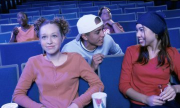 Teenage boys and girls watching a movie in a theater