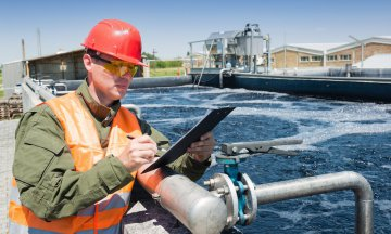An engineer controlling the quality of water , aerated activated sludge tank at a waste water treatment plant