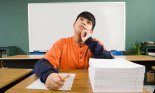 Schoolboy thinking, with a stack of notepaper on his desk