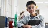 Boy standing beside assorted beakers in school laboratory