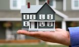 Hand Holding Model House in front of Full Size Home