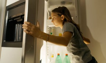 Girl looking into the refrigerator