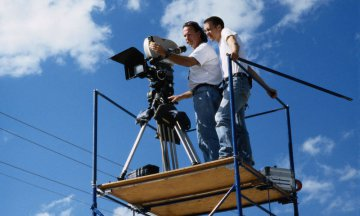 Cameraman and assistant on scaffolding with camera