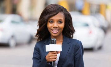 Female news reporter working outdoors while cars drive by