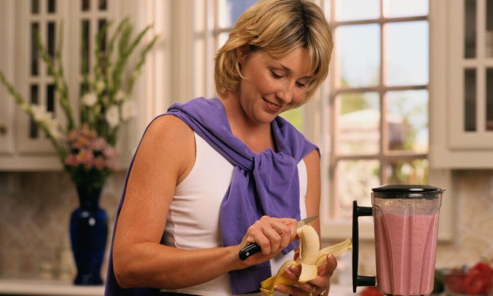woman making healthful blender drink