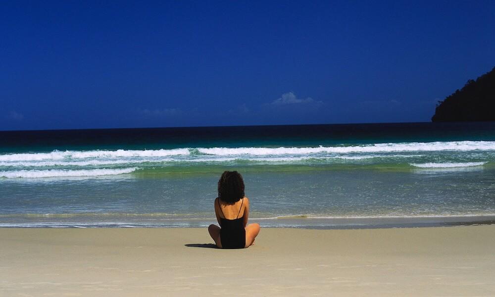 Woman Sitting on a Sandy Beach