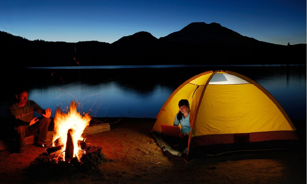 Camping couple by the fire on Sparks Lake shore