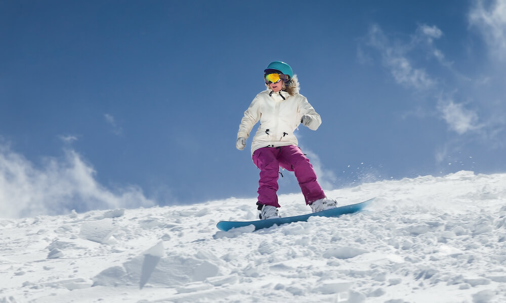 Young girl snowboarder in motion on snowboard