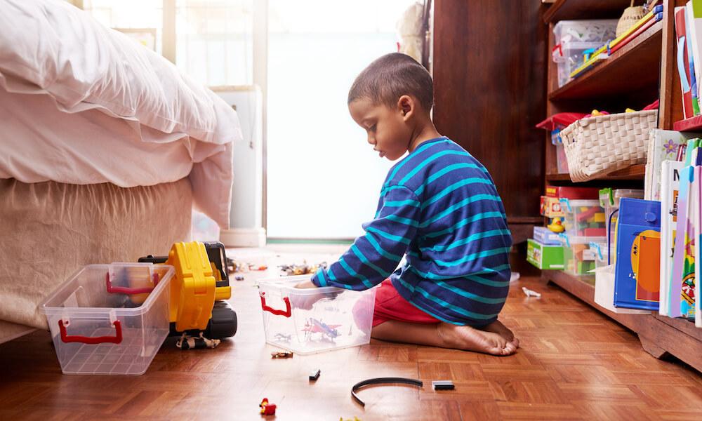 Young boy putting aways toys