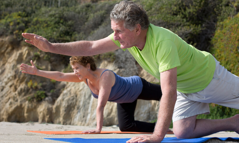 Caucasian couple practicing yoga on beach
