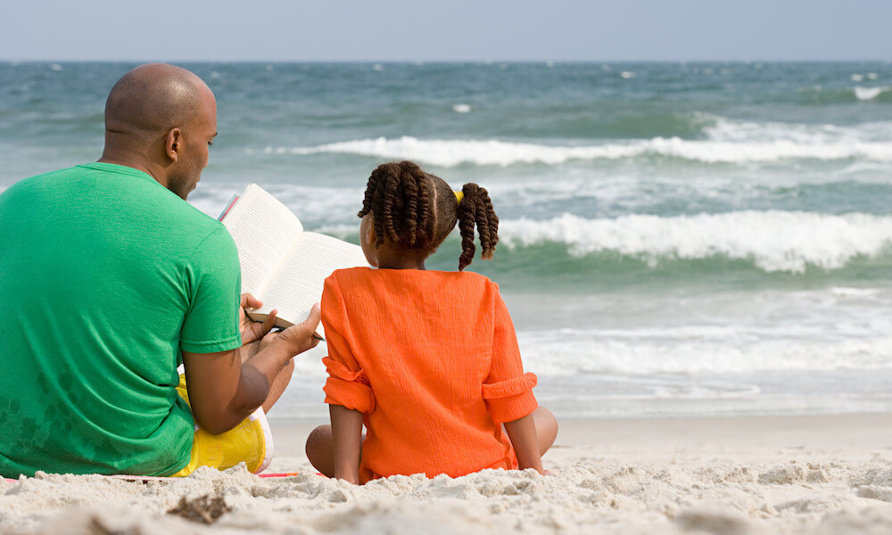 Father and daughter reading a book on the beach