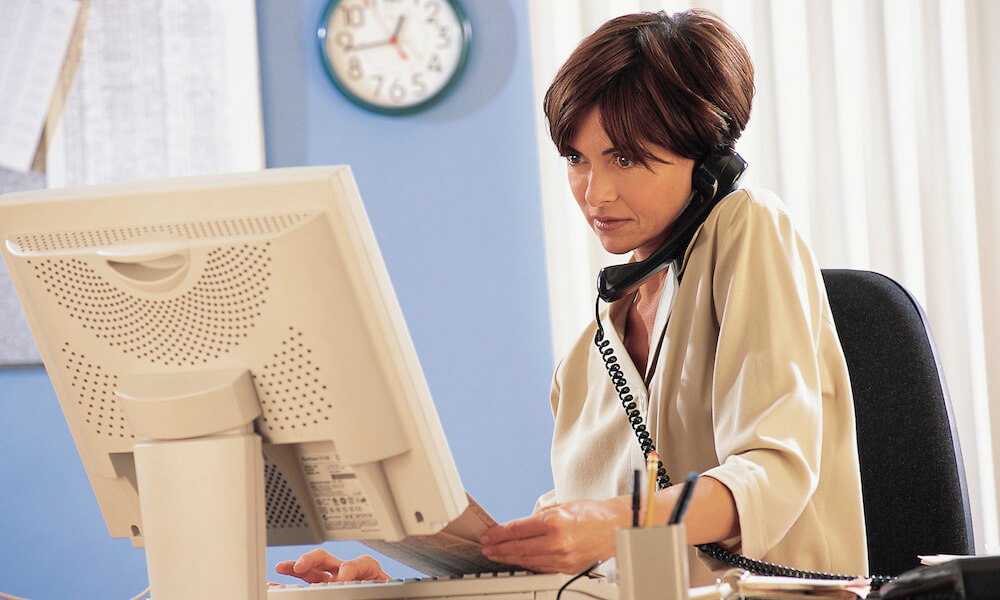 female office worker on phone in front of her computer