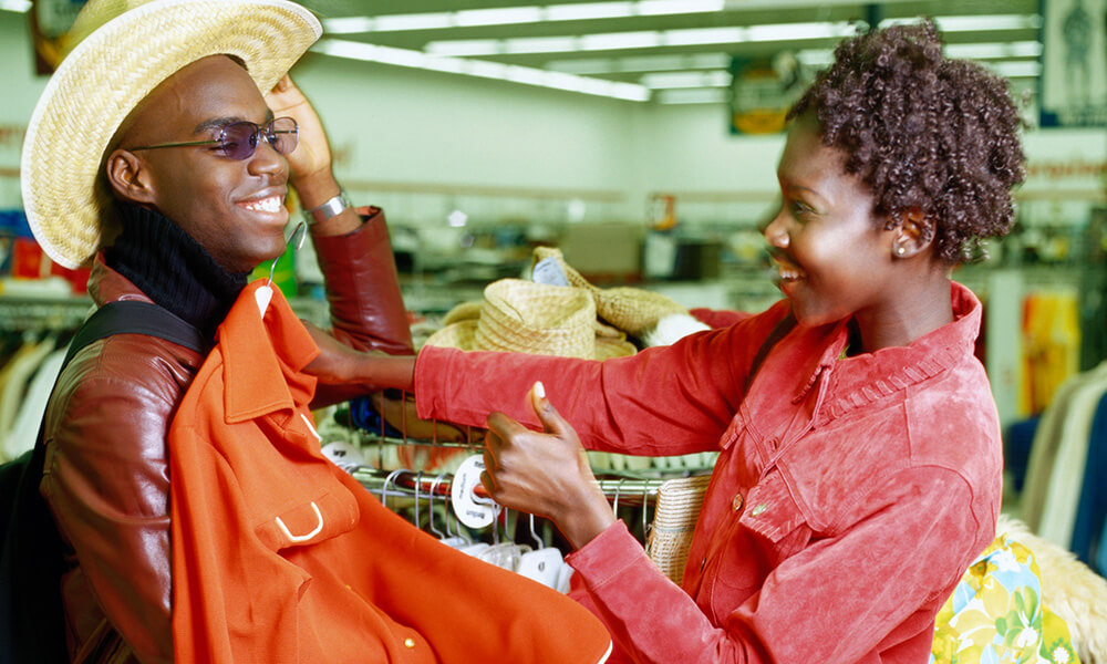 Young man and woman smiling as they look at clothes in a thrift store