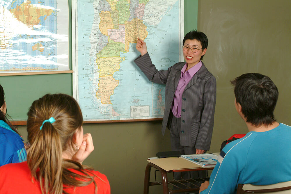 Geography teacher pointing at a map